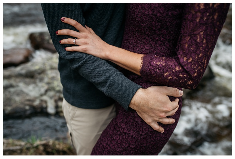 An engaged couple embraces at Rocky Mountain National Park near Estes Park, Colorado. Wedding engagement photography by Sonja Salzburg of Sonja K Photography.