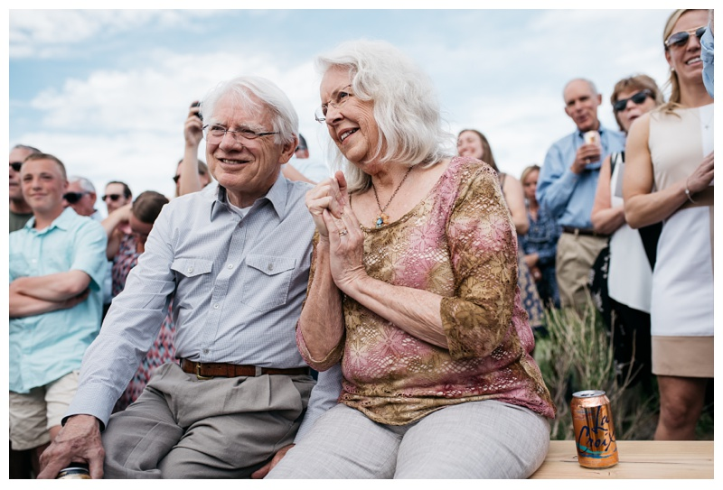 A grandfather and grandmother watch a wedding at Bingham Hill outside of Fort Collins, Colorado. Outdoor wedding photography by Sonja Salzburg of Sonja K Photography.
