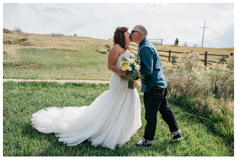 A bride and groom kiss at a wedding at Bingham Hill outside of Fort Collins, Colorado. Wedding photography by Sonja Salzburg of Sonja K Photography.