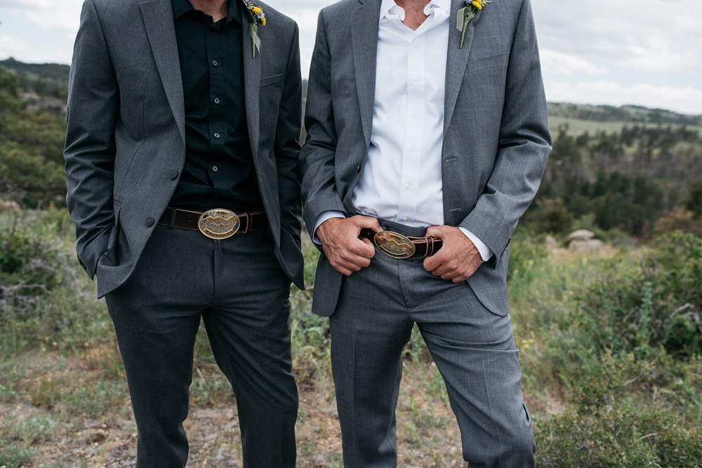 Custom made belt buckles for the groom and best man at a wedding near Vedauwoo near Cheyenne and Laramie, Wyoming. Wedding photography by Sonja Salzburg of Sonja K Photography.