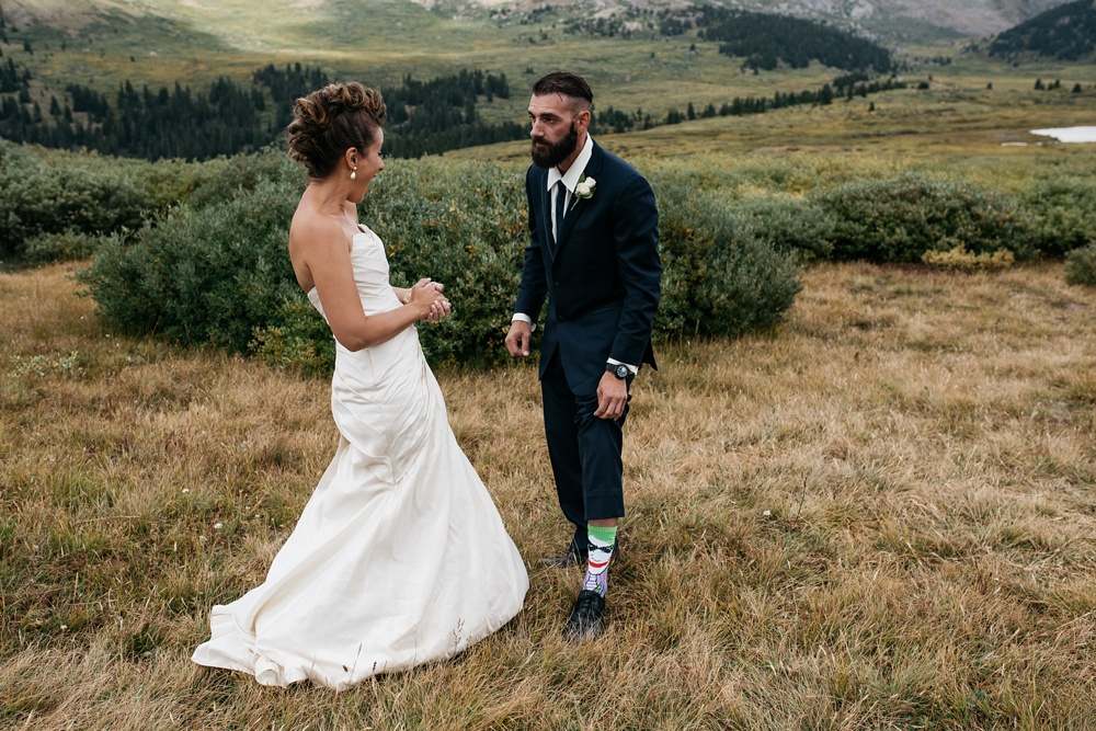 A groom shows off his Joker socks from Batman at a first look near Guanella Pass in Colorado. Wedding photography by Sonja Salzburg of Sonja K Photography.