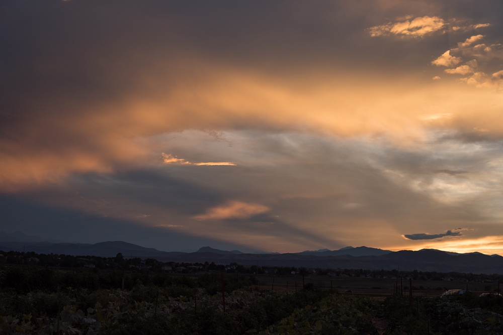 The sun sets over the Rocky Mountains at the Fortified Collaborations Harvest Moon Salmon Bake at Fossil Creek Farms in Fort Collins, Colorado. Event and food photography by Sonja Salzburg of Sonja K Photography.