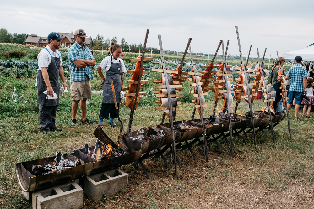 Salmon is cooked on poles by Jax Fish House and Oyster Bar at the Fortified Collaborations Harvest Moon Salmon Bake at Fossil Creek Farms in Fort Collins, Colorado. Event photography by Sonja K Photography.