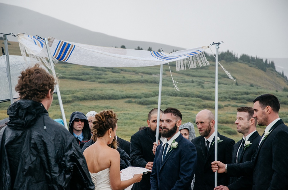 A bride and groom exchange vows at a Jewish wedding on top of Guanella Pass outside of Georgetown, Colorado. Wedding photography by Sonja Salzburg of Sonja K Photography.