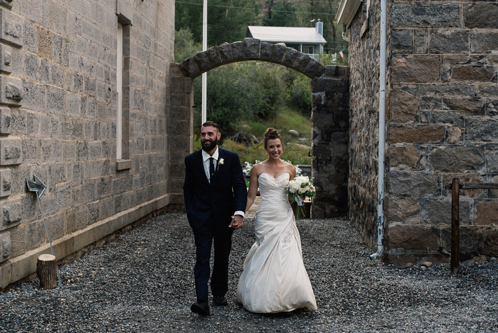 A bride and groom enter their reception at the historic Hamill House in Georgetown, Colorado. Wedding photography by Sonja Salzburg of Sonja K Photography.