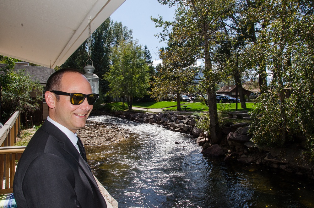 The groom gets ready for his wedding along the banks of the Big Thompson River in Estes Park, Colorado. Wedding photography by Sonja Salzburg of Sonja K Photography.