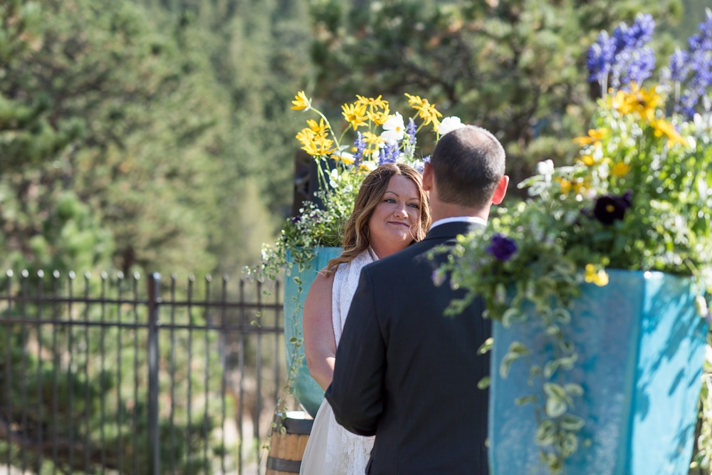 A bride and groom get married at an outdoor wedding ceremony at the Historic Crags Lodge near Rocky Mountain Park in Estes Park, Colorado. Wedding photography by Sonja Salzburg of Sonja K Photography.