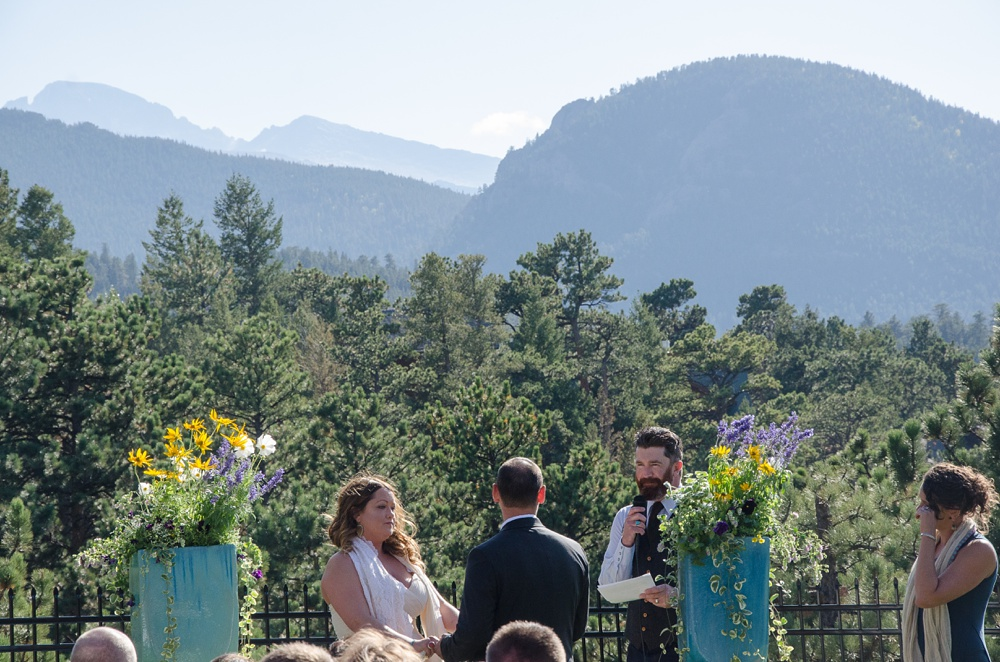 An outdoor wedding ceremony at the Historic Crags Lodge with Longs Peak in the distance in Estes Park, Colorado. Rocky Mountain National Park wedding photography by Sonja Salzburg of Sonja K Photography.