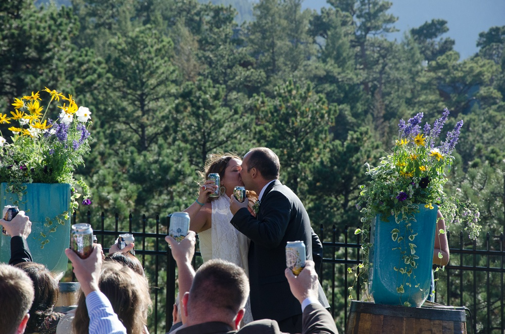 A newly married couple cheers and kisses at an outdoor wedding ceremony at the Historic Crags Lodge in Estes Park, Colorado. Rocky Mountain National Park wedding photography by Sonja Salzburg of Sonja K Photography.