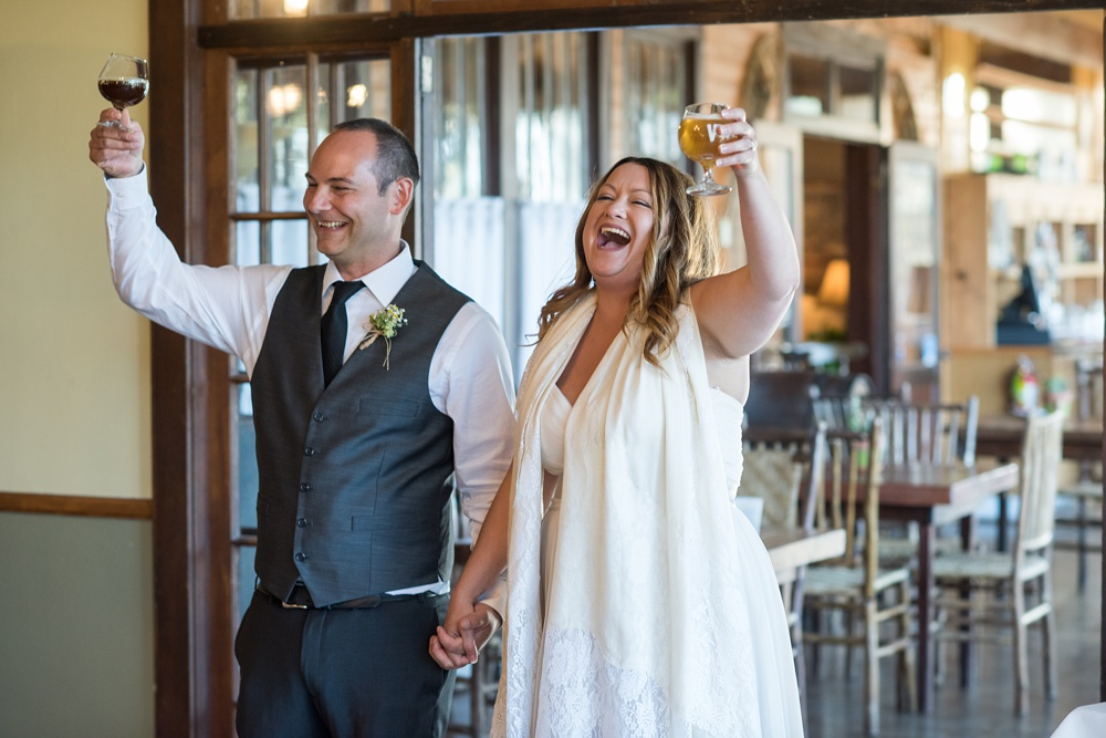 A newly married couple cheers their guests at the Historic Crags Lodge in Estes Park, Colorado. Wedding photography by Sonja Salzburg of Sonja K Photography.