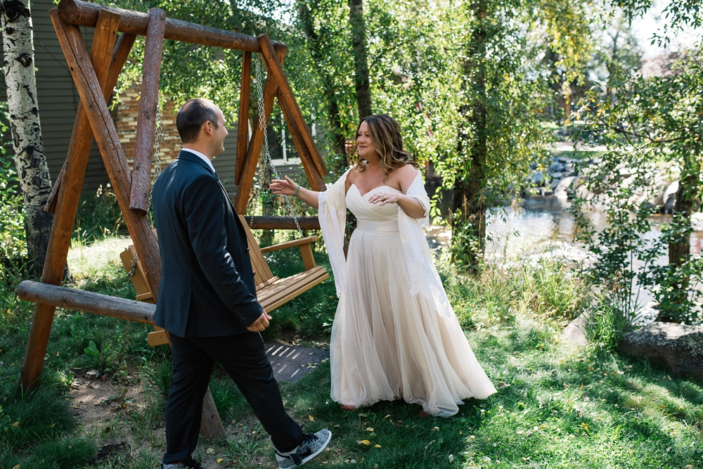 A bride and groom at their first look along the banks of the Big Thompson River in Estes Park, Colorado. Wedding photography by Sonja Salzburg of Sonja K Photography.