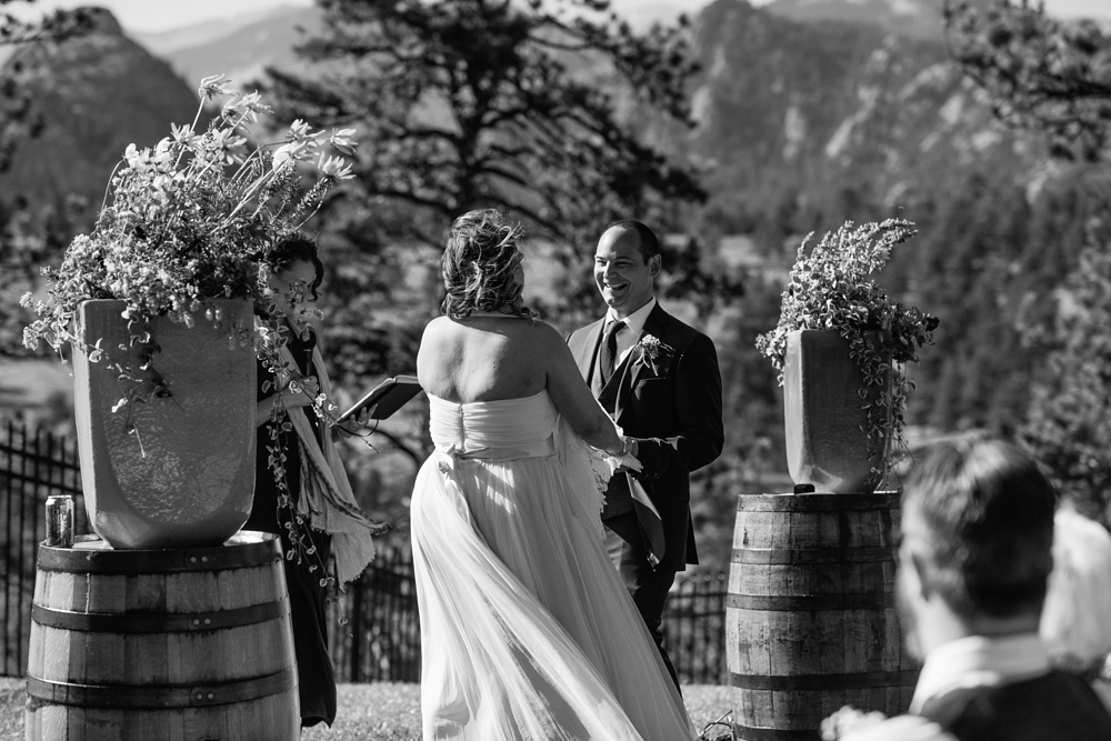 A black and white photo of an outdoor wedding ceremony at the Historic Crags Lodge near Rocky Mountain National Park in Estes Park, Colorado. Wedding photography by Sonja Salzburg of Sonja K Photography.