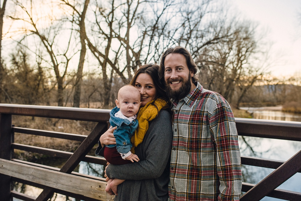 A young family on a bridge over the Poudre River on a warm late fall evening at Legacy Park in Fort Collins, Colorado. Family portrait photography by Sonja Salzburg of Sonja K Photography.