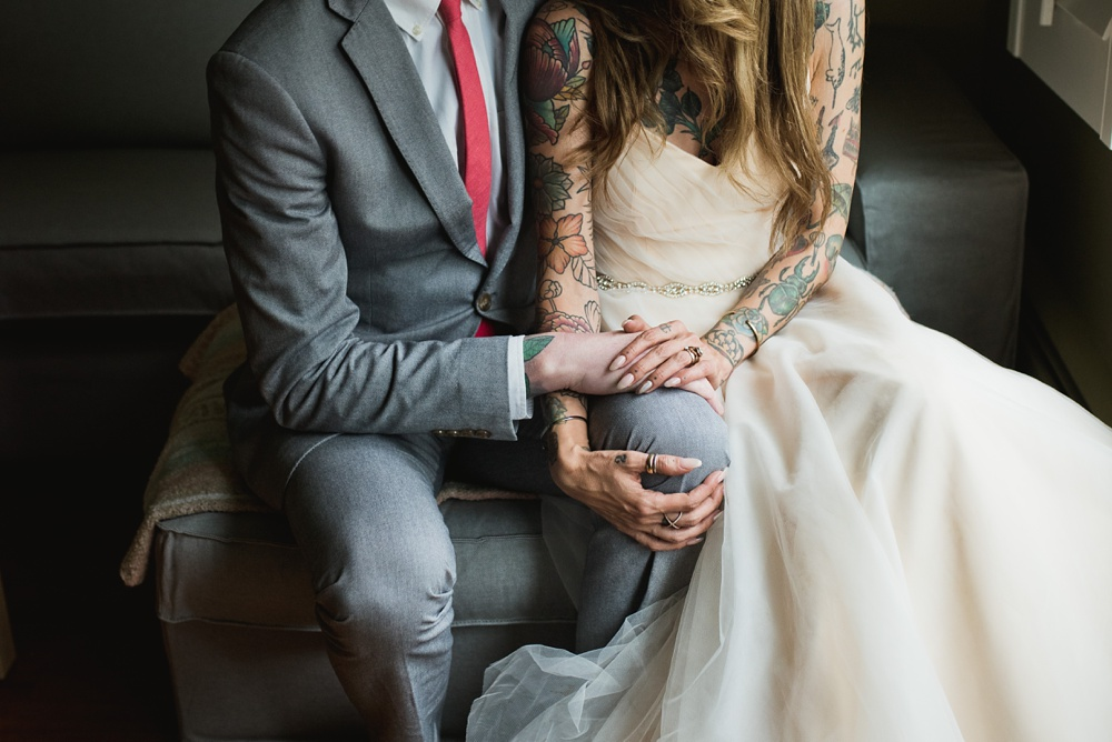 A tattooed bride and her husband relax in their home on their wedding day in Fort Collins, Colorado. Wedding photography by Sonja Salzburg of Sonja K Photography.