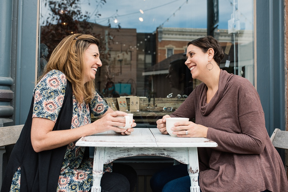 Two doulas have coffee in Old Town Fort Collins on a sunny day. Personal branding and headshot photography by Sonja Salzburg of Sonja K Photography.