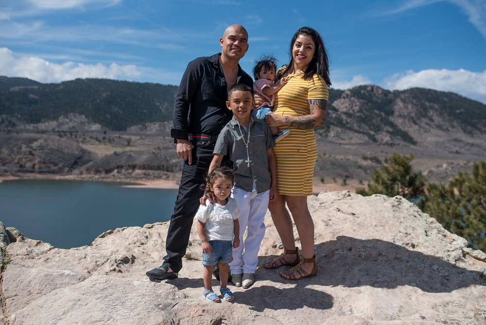 A young family on Duncan Ridge above Horsetooth Reservoir outside of Fort Collins, Colorado. Family portrait photography by Sonja Salzburg of Sonja K Photography.