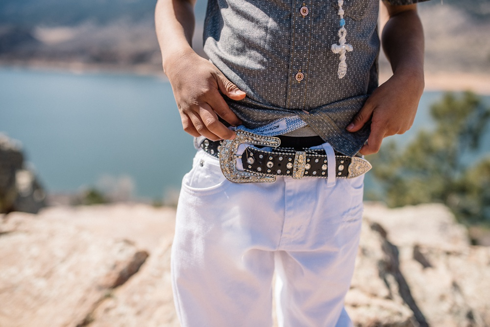A child shows off his sweet belt at Duncan Ridge near Horsetooth Reservoir outside of Fort Collins, Colorado. Family portrait photography by Sonja Salzburg of Sonja K Photography.