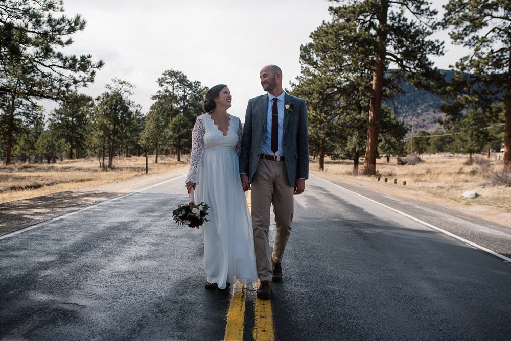 A bride and groom on the road on their wedding day in Rocky Mountain National Park in Colorado. Elopement wedding photography by Sonja Salzburg of Sonja K Photography.