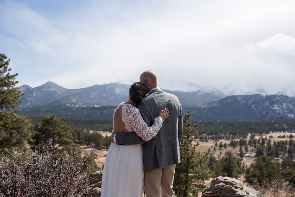 A bride and groom look over the mountains on their wedding day in Rocky Mountain National Park in Colorado. Elopement wedding photography by Sonja Salzburg of Sonja K Photography.