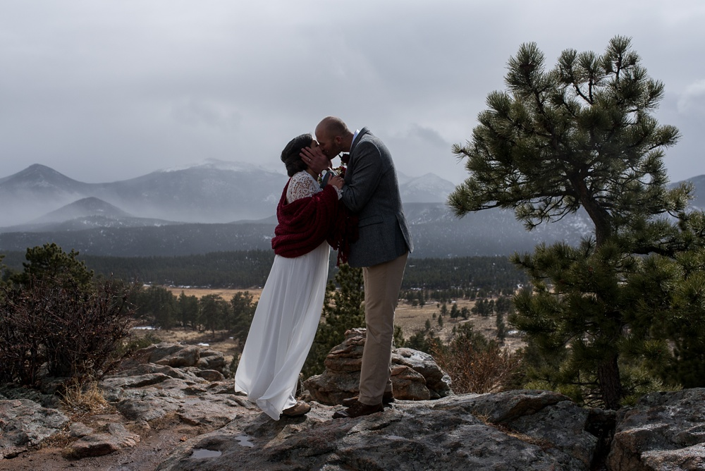 A newly married couple kiss at their elopement ceremony at 3M Curve in Rocky Mountain National Park. Elopement wedding photography by Sonja Salzburg of Sonja K Photography.