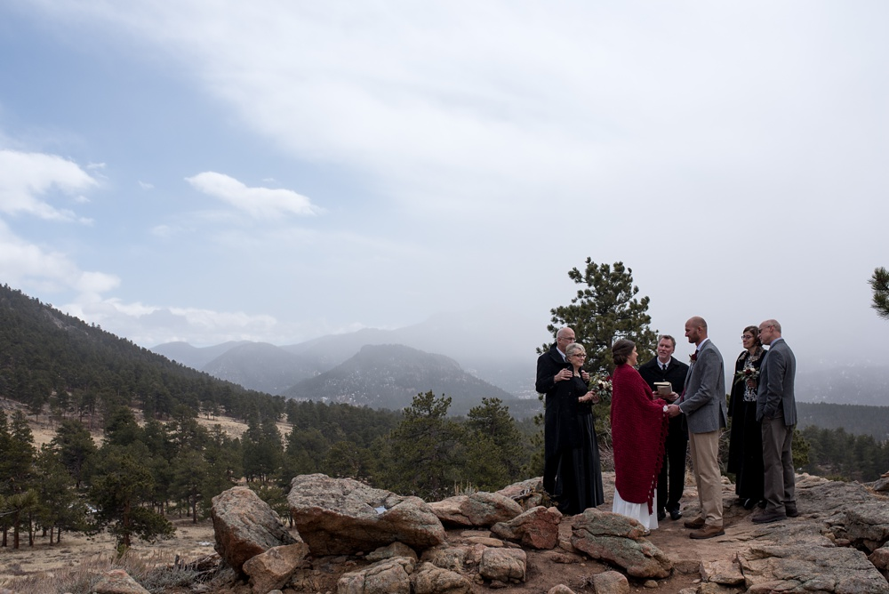 A bride and groom with their family get married at 3M Curve in an elopement at Rocky Mountain National Park in Colorado.  Elopement wedding photography by Sonja Salzburg of Sonja K Photography.