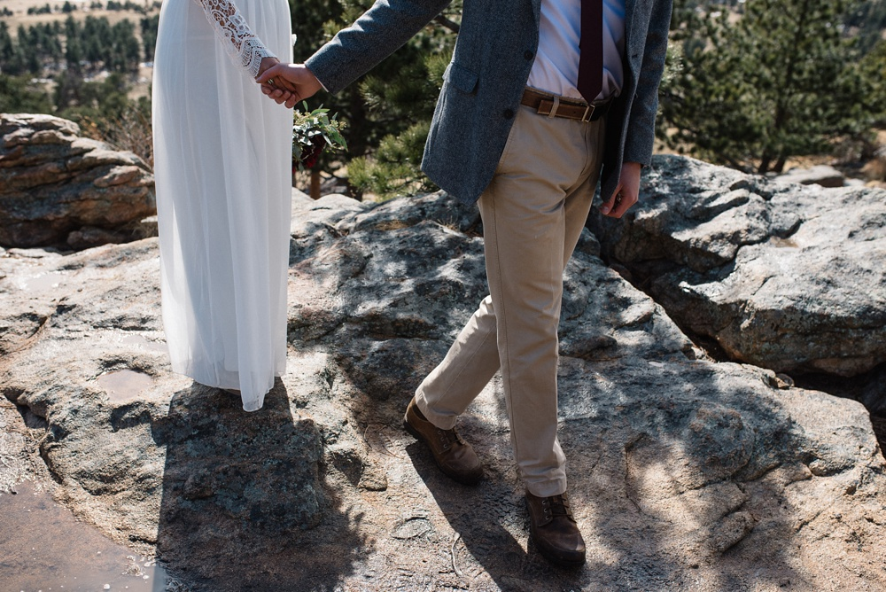 a bride and groom hold hands at their elopement ceremony site in Rocky Mountain National Park at 3M Curve photographed by Sonja K Photography