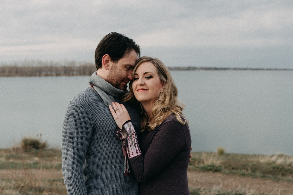 An engaged couple at a session at Standley Lake in Westminster, Colorado. Engagement portrait photography by Sonja Salzburg of Sonja K Photography.