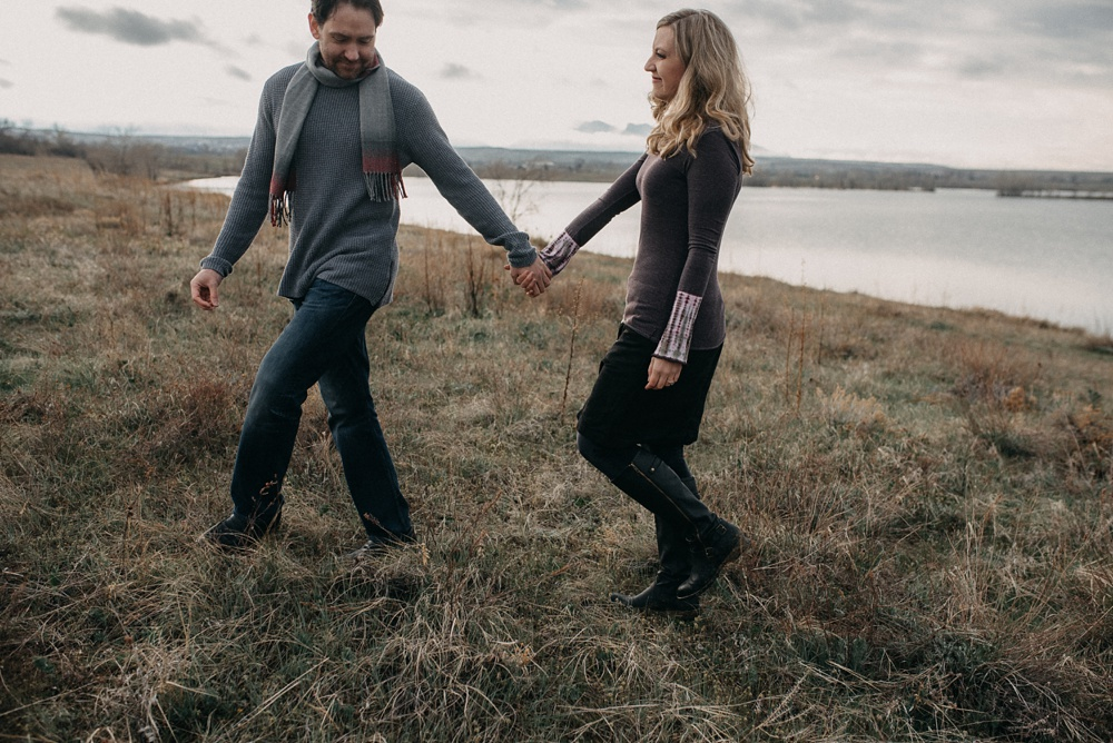 A couple is engaged at Standley Lake in Westminster, Colorado. Engagement and family portraits by Sonja Salzburg of Sonja K Photography.