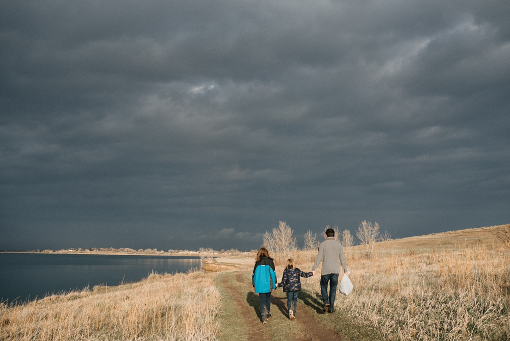 A young family walks to their car at Standley Lake in Westminster, Colorado. Family portrait photography by Sonja Salzburg of Sonja K Photography.
