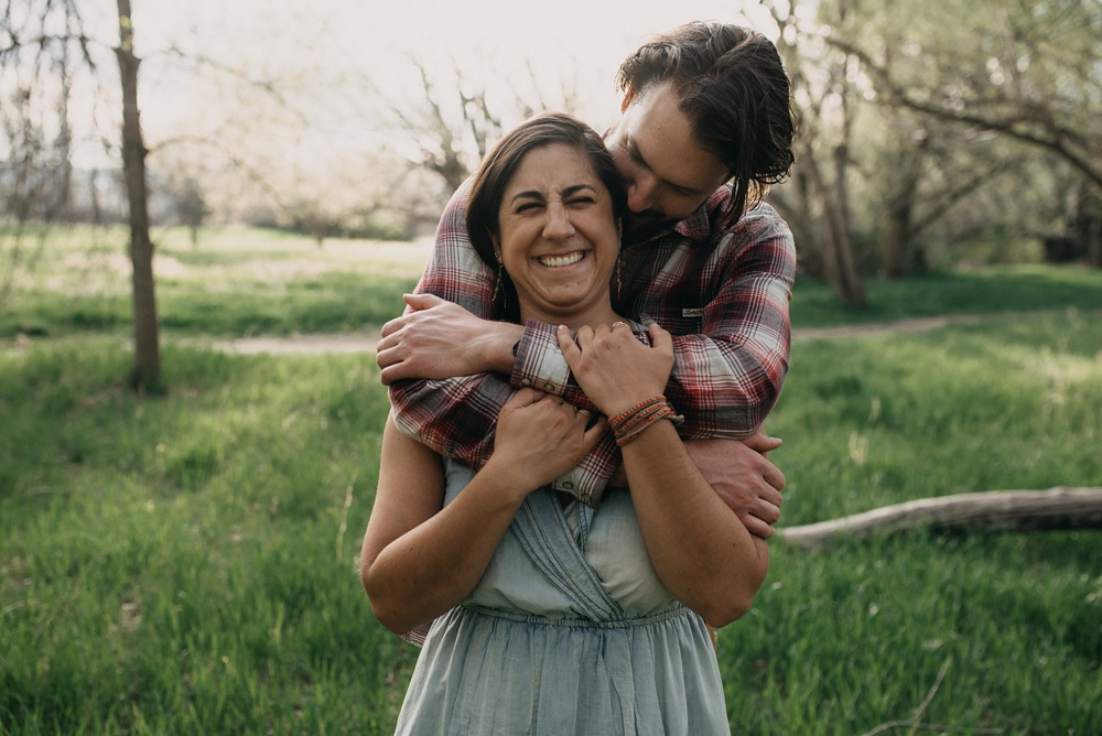 A happily engaged couple at an engagement session at Lee Martinez Park in Fort Collins, Colorado. Engagement portrait photography by Sonja Salzburg of Sonja K Photography.