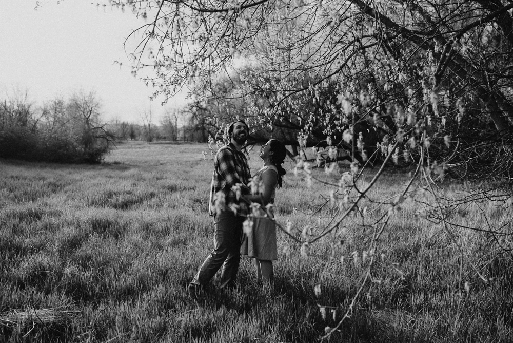 A black and white photo of a newly engaged couple at Lee Martinez Park in Fort Collins, Colorado. Engagement portrait photography by Sonja Salzburg of Sonja K Photography.