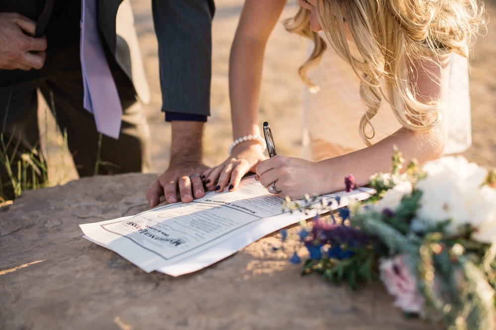 A couple signs their marriage license at an elopement at Horsetooth Reservoir outside of Fort Collins, Colorado. Elopement photography by Sonja Salzburg of Sonja K Photography.