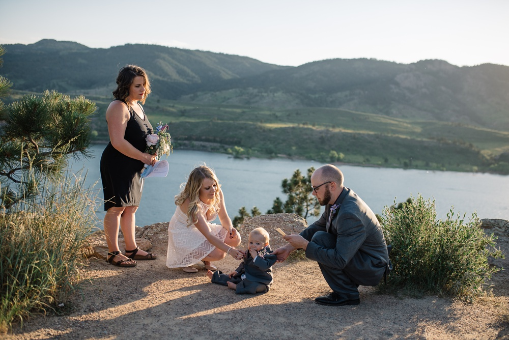 A young couple reads vows to their son at their wedding at Horsetooth Reservoir outside of Fort Collins, Colorado. Wedding photography by Sonja Salzburg of Sonja K Photography.