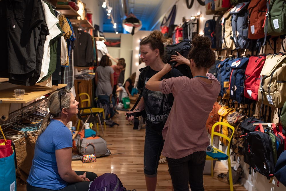 A participant gets fitted with a backpack at the Wellbody Woman Summer TRIBE Program at Topo Designs in Old Town Fort Collins, Colorado. Corporate event photography by Sonja Salzburg of Sonja K Photography.