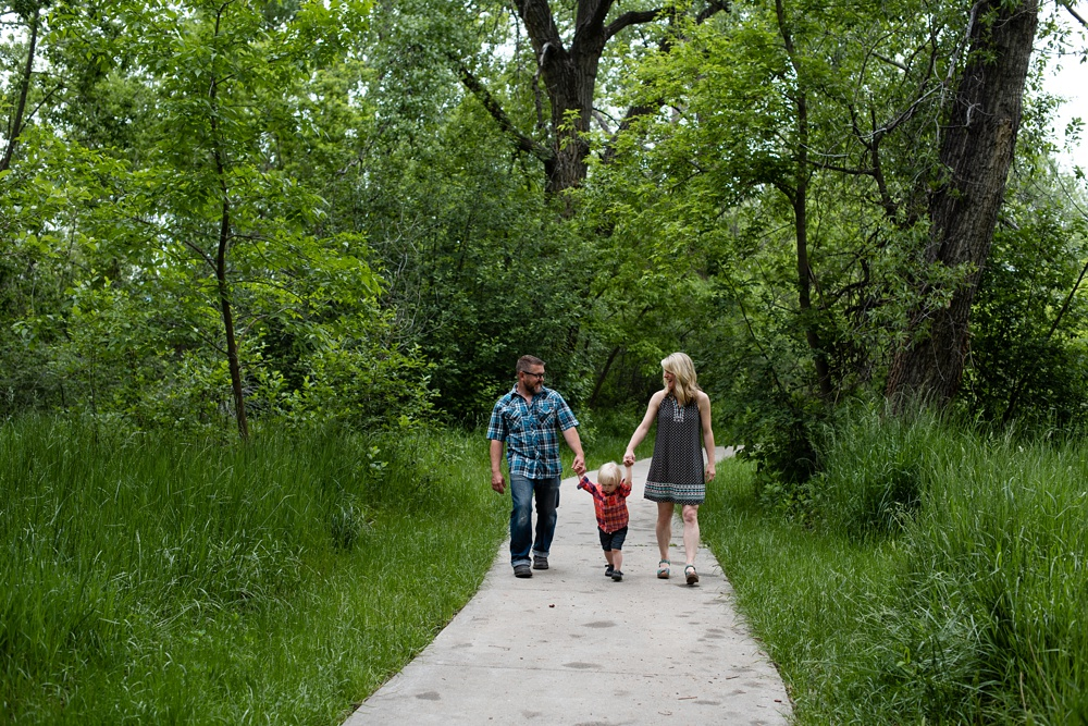 A young family walks along the trail at Watson Lake outside of Fort Collins, Colorado. Family portrait photography by Sonja Salzburg of Sonja K Photography.