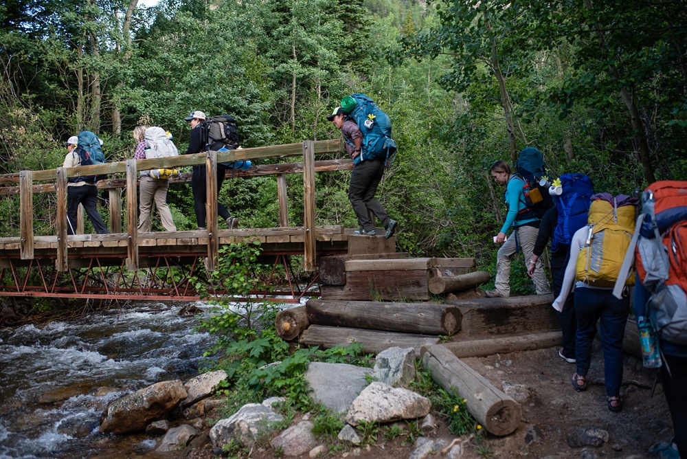 The hiking group cross the middle fork of Boulder Creek at the Wellbody Women Summer TRIBE Program in Indian Peaks Wilderness in Colorado. Outdoor event photography by Sonja Salzburg of Sonja K Photography.
