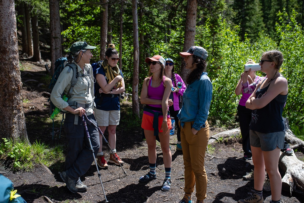 Backpackers take a break on a hike in the Indian Peaks Wilderness on the Wellbody Woman Summer TRIBE Program. Outdoor event photography by Sonja Salzburg of Sonja K Photography.