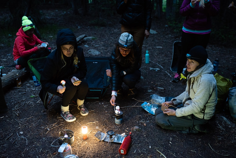 Participants in the Wellbody Woman Summer TRIBE Program make smores over a backpacking stove. Outdoor event photography by Sonja Salzburg of Sonja K Photography.