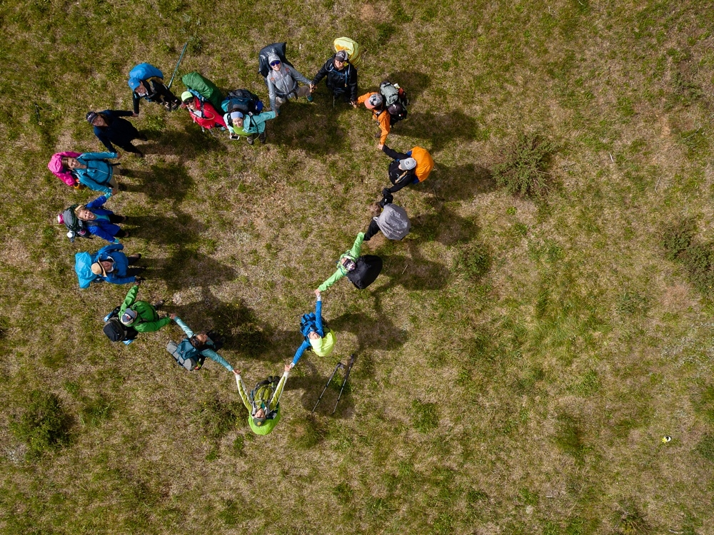 The participants of the Sumer TRIBE Program by Wellbody Woman form a heart in the Indian Peaks Wilderness in Colorado. Outdoor event photography by Sonja Salzburg of Sonja K Photography.