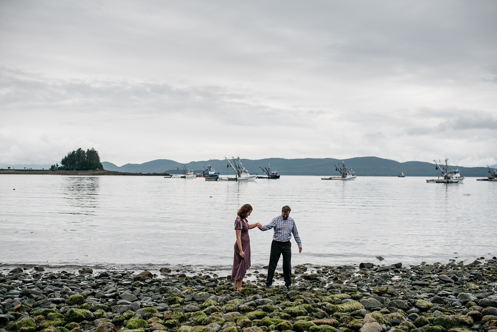 A young engaged couple near the fishing fleet at the Jensen Olson Arboretum outside of Juneau, Alaska. Engagement portrait photography by Sonja Salzburg of Sonja K Photography.