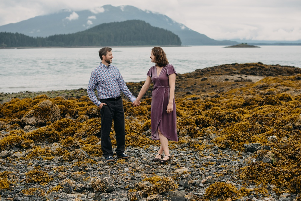 An engaged couple on a rocky beach near Juneau, Alaska. Engagement portrait photography by Sonja Salzburg of Sonja K Photography.