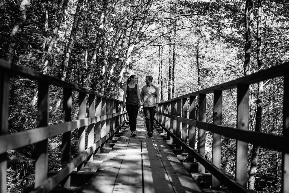 An engaged couple walk on the Gold Creek Flume Trail outside of Juneau, Alaska. Engagement portrait photography by Sonja Salzburg of Sonja K Photography.