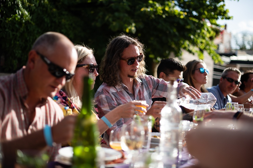 Patrons enjoy their dinner on a sunny evening at the Fortified Collaborations Second Sunday Supper in Montezuma Fuller Alley in Fort Collins, Colorado. Event and Food and Beverage Photography by Sonja Salzburg of Sonja K Photography.