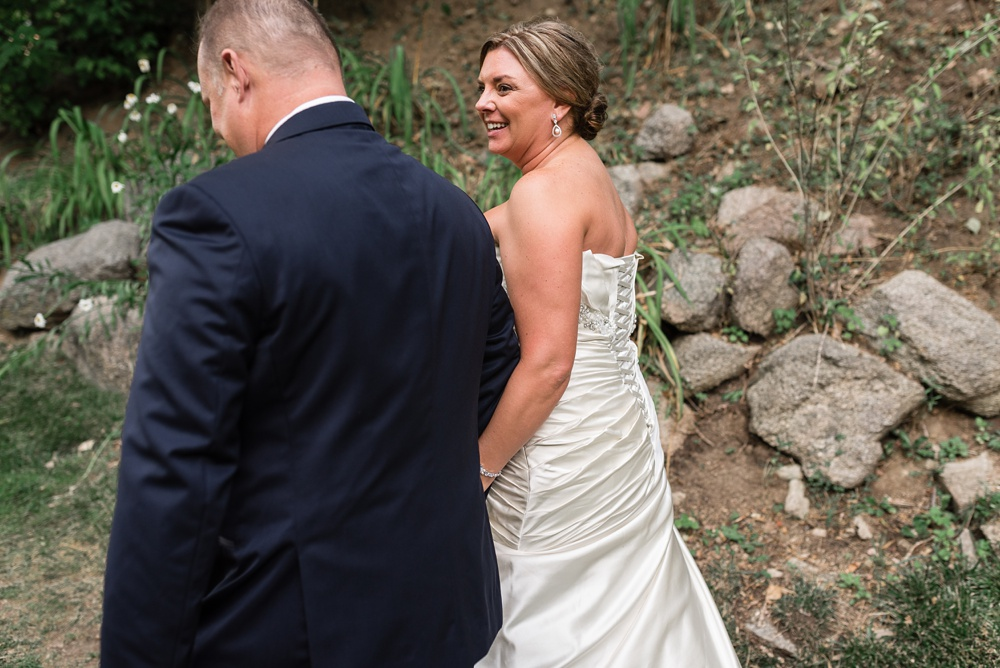 A bride and groom leave their wedding ceremony at Wedgewood Weddings on Boulder Creek outside of Boulder, Colorado. Wedding photography by Sonja Salzburg of Sonja K Photography.