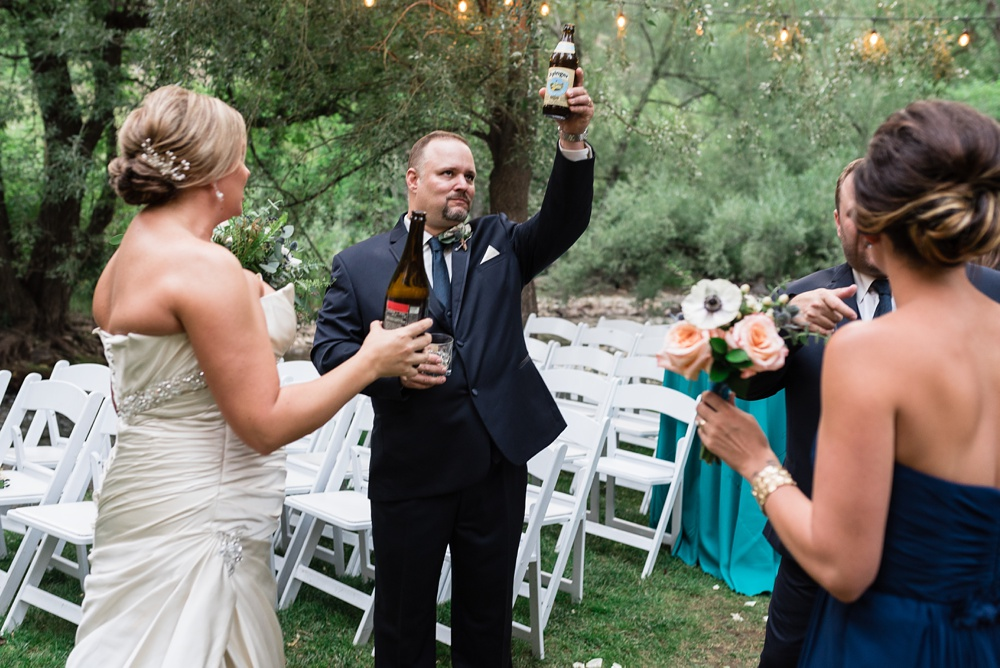 A bide and groom share a craft beer at their wedding at Wedgewood Weddings on Boulder Creek outside of Boulder, Colorado. Wedding photography by Sonja Salzburg of Sonja K Photography.