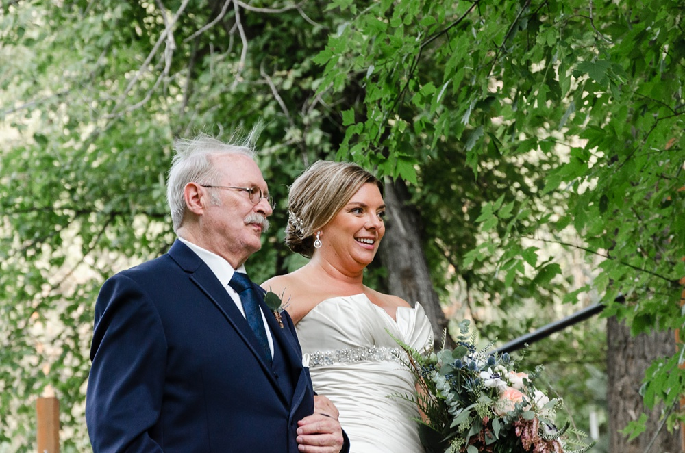 A bride and her father walk down the aisle together at a wedding at Wedgewood Weddings on Boulder Creek outside of Boulder, Colorado. Wedding portrait photography by Sonja Salzburg of Sonja K Photography.