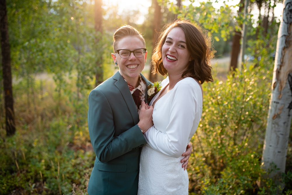 A young lesbian couple on their wedding day outside of Fraser, Colorado. Wedding photography by Sonja Salzburg of Sonja K Photography.