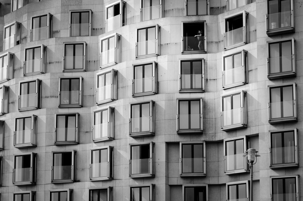 City Living - architectural photo of windows and one person smoking taken in Berlin