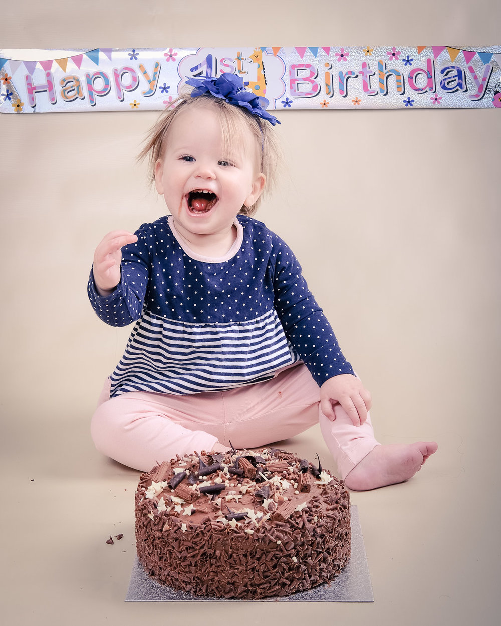 First birthday Smash the Cake photo shoot, girl eating cake with big smile on her face