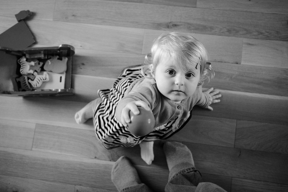 Family photography of Isla passing a ball looking up directly at the camera. Taken in Nottingham in black and white.